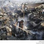 سكان الأحياء الفقيرة يحاولون إخماد حريق في دكا