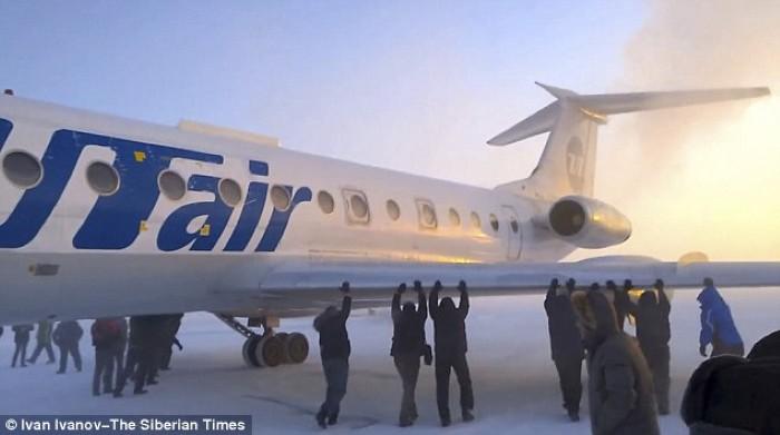 ركاب يدفعون طائرة في سيبيريا