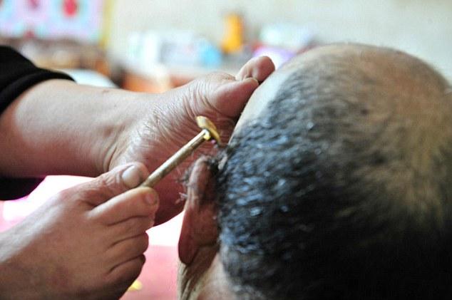 زوجة مشلولة تستعين بأقدامها لحلق شعر زوجها
