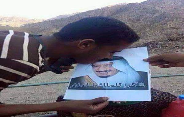 رجل يمني يقبل صورة لخادم الحرمين الشريفين