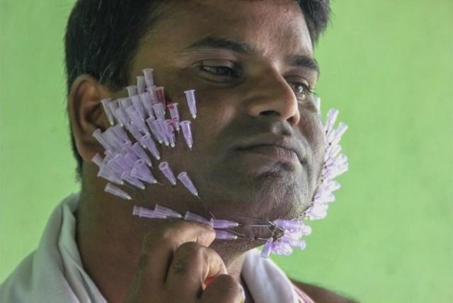 هندي يغرز مئات الابر في وجهه