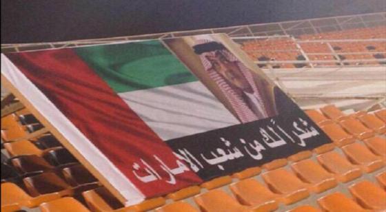 جماهير نادي عجمان الإماراتي ترفع لافتات عليها علم دولتها مع شكر لعميد الدبلوماسيين
