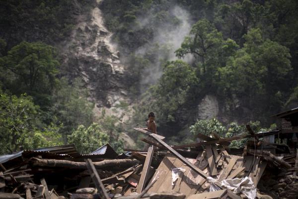 صبي يزيل الأنقاض من على منزله في نيبال.