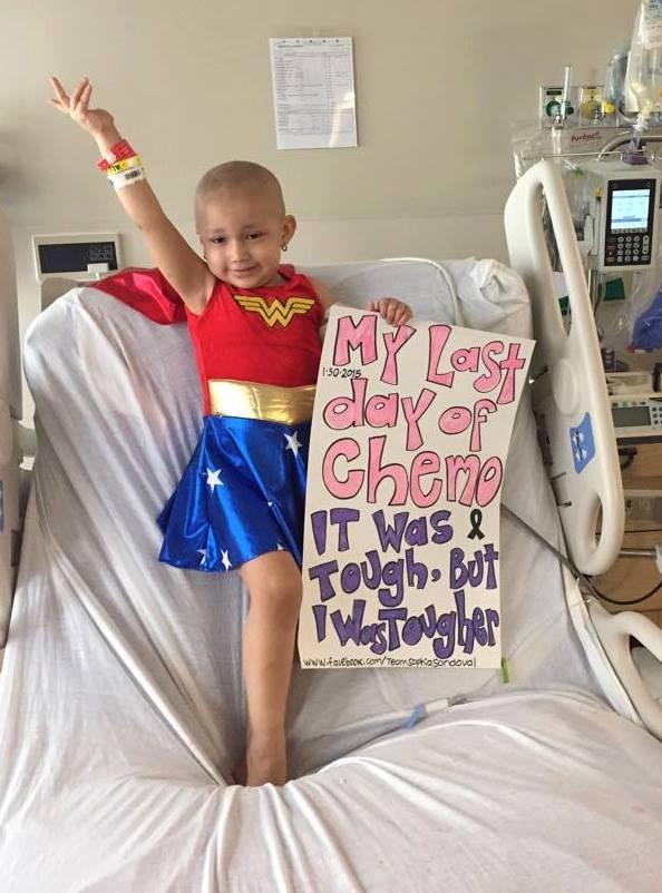 """طفلة مصابة بالسرطان تحمل لافتة تقول """" هذه آخر جرعة للعلاج الكيميائي، كانت قوية لكنني كنت أقوى"""""""