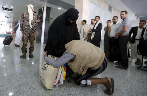 رجل يمني يقبل قدمي أمه فرحا واستهلالا بها بعد وصوله لمطار صنعاء قادما من مصر