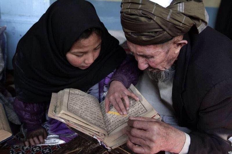 طفلة أفغانية تتعلم قراءة القرآن الكريم