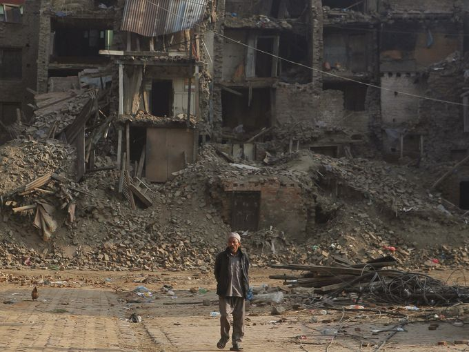 رجل نيبالي يمشي بين الركام بفعل الزلزال الذي ضرب النيبال الشهر الماضي