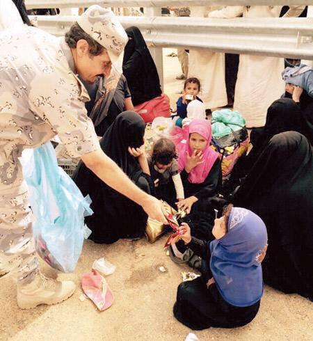 ضابط في حرس الحدود يوزع أغذية على نازحين يمنيين بمنفذ الوديعة أمس