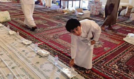 أطفال يشاركون في تجهيز مائدة الإفطار في المواقع المتخصصة بإفطار الصائمين بعرعر