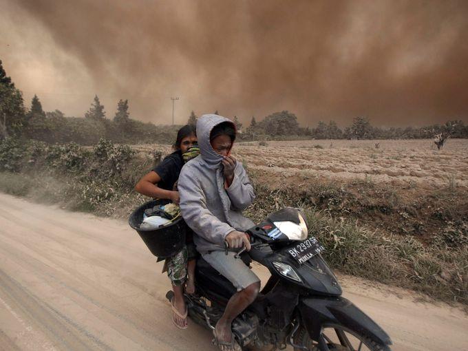 """صور حول العالم قرويون يغطون وجوههم بالقرب من """"سوكانديبي"""" بعد أن نفث بركان جبل سينابونغ الرماد والغازات السامة"""