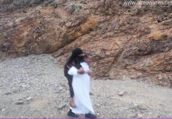 شاب في نزهة يحمل أمه المسنة على ظهره والتي لم تستطيع المشي في إحدى قرى منطقة عسير.