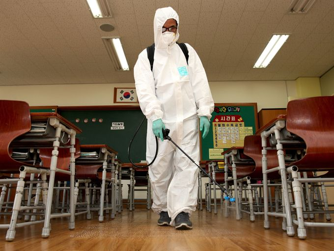 عامل صحة يرتدي زيا واقيا ويقوم برش بخاخ واقي في الفصول المدرسية في سيول