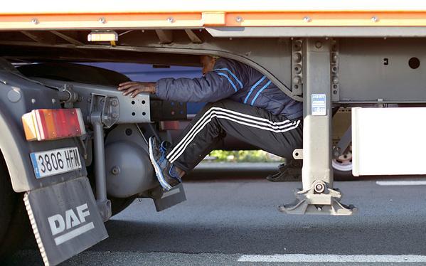 مهاجر يحاول الاختباء تحت شاحنة