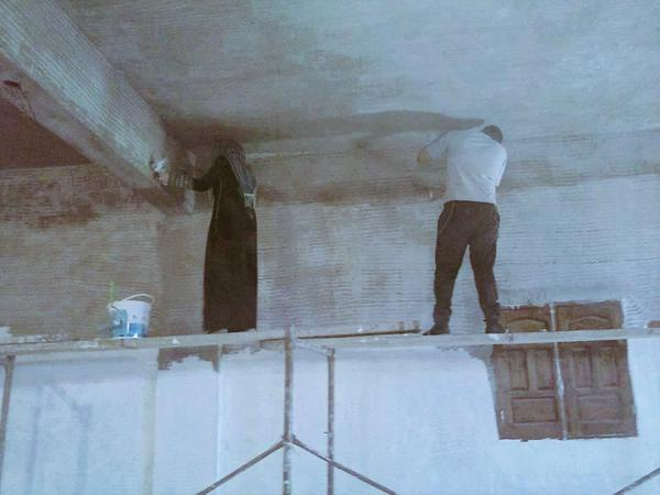 سيدة من غزة تساعد زوجها في أعمال البناء.