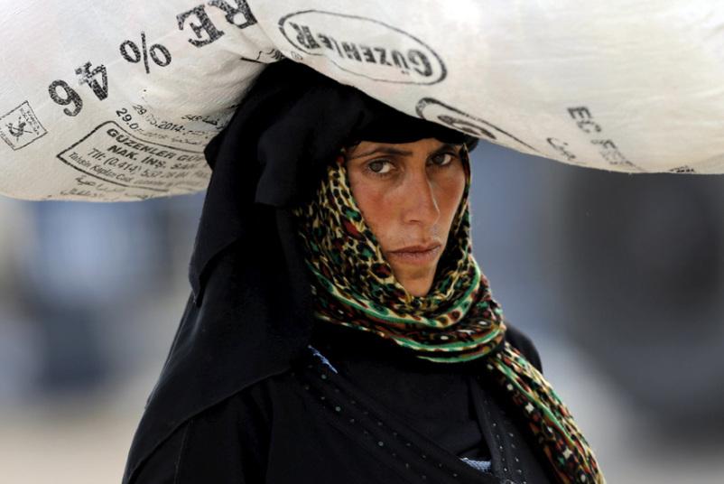 لاجئة سورية تحمل أمتعتها على رأسها أثناء عبورها بوابة تفصل بين الحدود التركية والسورية في محافظة سانليورفا.