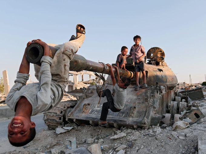 أطفال يلهون على دبابة مدمرة جنوب سيدات سونا.
