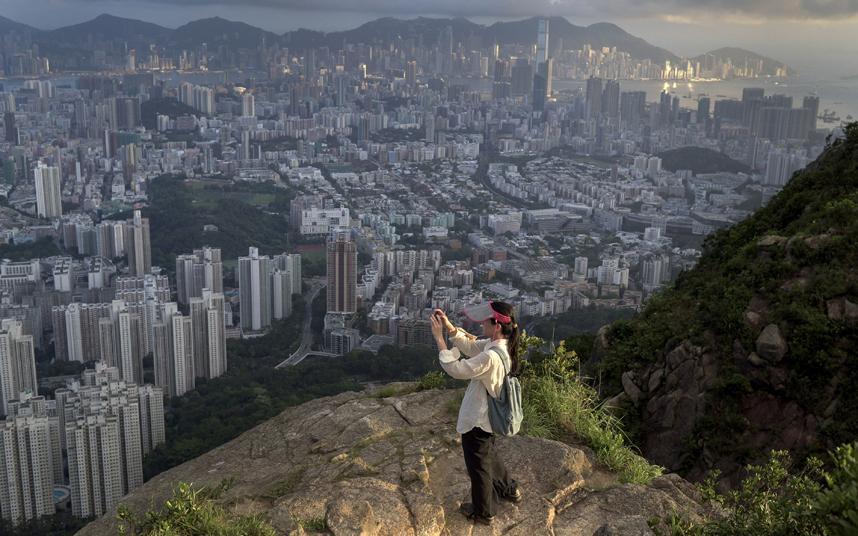 مسافر في هونج كونج يأخذ صورة للمدينة من ممر للمشي.