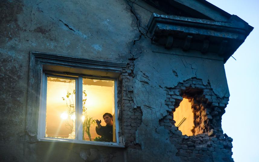 مواطن يتفقد منزله الذي تعرض للقصف بسبب المعارك الادئرة بين الإنفصاليين المدعومين من روسيا والقوات الحكومية الأوكرانية في دونتيسك.