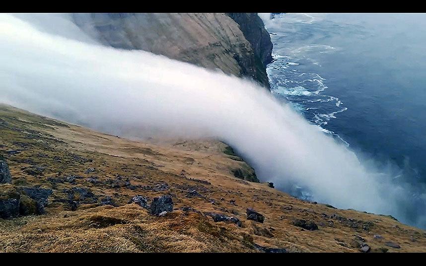 صور حول العالم نهر من الضباب ينحدر على حافة جرف وصولا إلى البحر جنوب آيسلندا