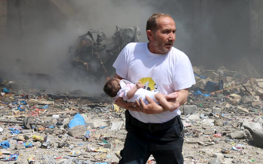 رجل يحمل طفل رضيع في محاولة للهروب من البراميل المتفجرة التي يلقيها النظام السوري على الأحياء الموالية للمعارضة السورية في مدينة حلب القديمة.