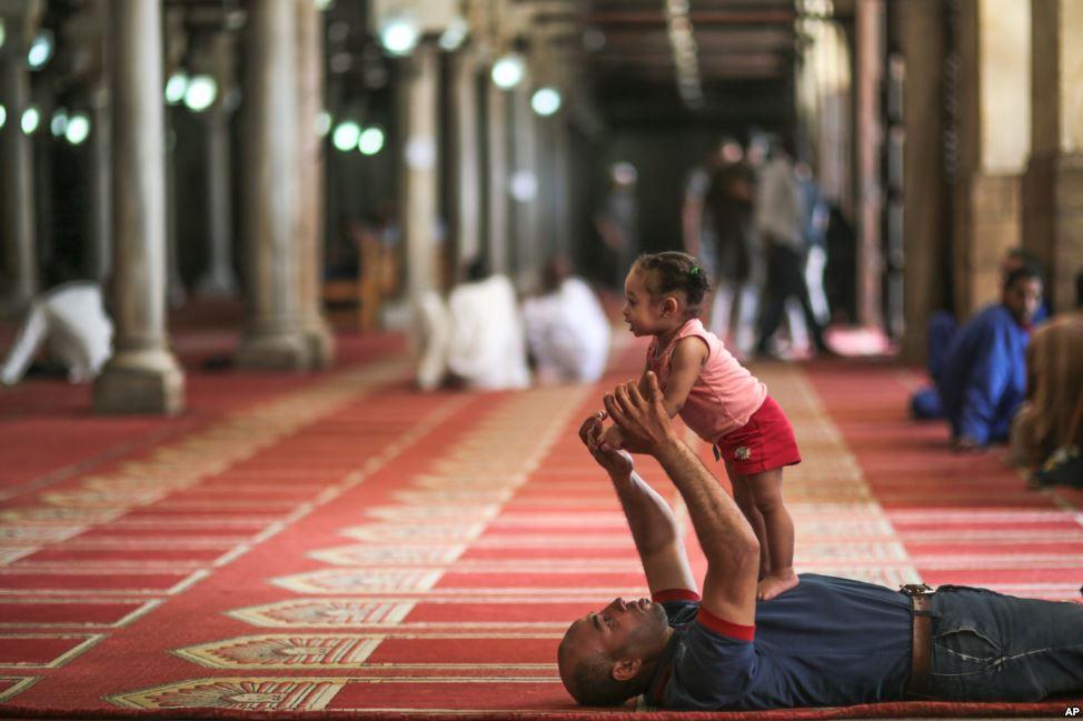رجل يلاعب ابنته الصغيرة بعد صلاة الظهر في الجامع الأزهر بالقاهرة.