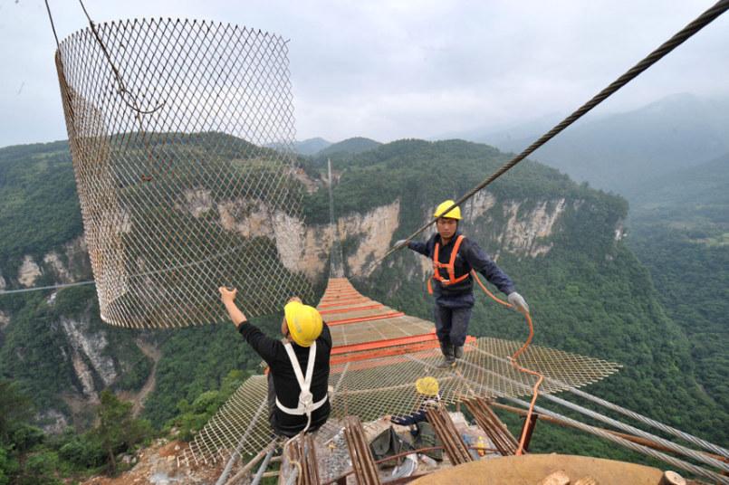 عمال يقومون بإنشاء جسر زجاجي عملاق جديد