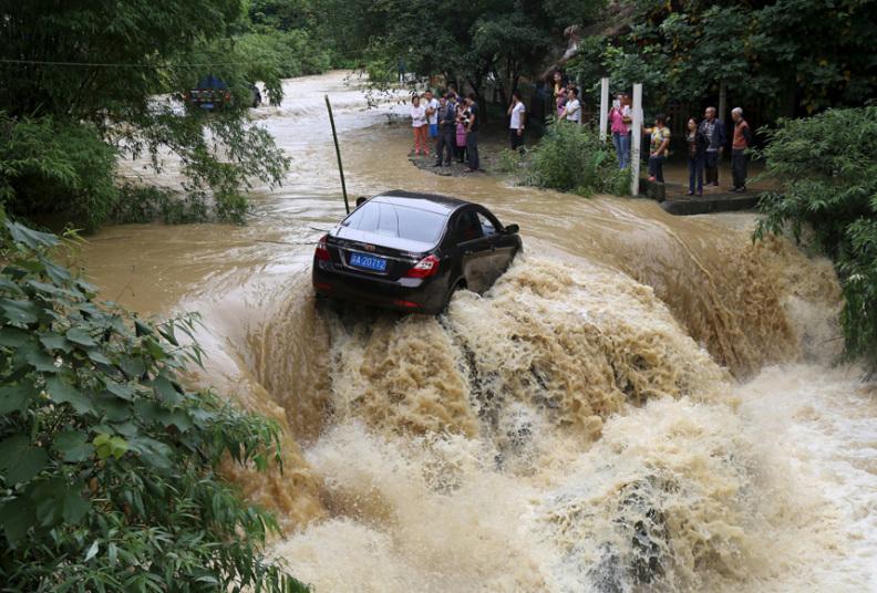 عمال يحاولون إزالة سيارة عالقة في نهر غمرته المياه