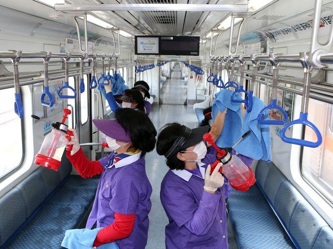 """عمال صحة يرتدون أقنعة يقومون بتعقيم الأماكن العامة كإجراء احترازي ضد مرض MERS أو ما يُعؤف بإسم """"فيروس الجهاز التنفسي في الشرق الأوسط"""" في مترو الأنفاق في بوسان."""