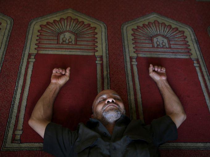أحد المصلين المسلمين يستلقي على الأرض في الجامع الأزهر بانتظار الصلاة