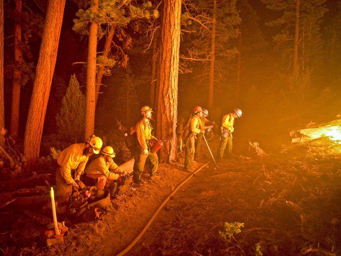 أفراد طاقم الدفاع المدني يقومون بإخماد حرائق ضخمة شبت في غابات مقاطعة سان بيرناردينو، كاليفورنيا