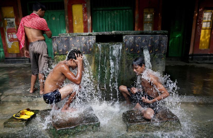 سكان محليون يستحمون في الطرقات والأماكن العامة للتخفيف من حرارة الجسم المرتفعة بفعل ارتفاع درجات الحرارة الحاد في كلكتا.