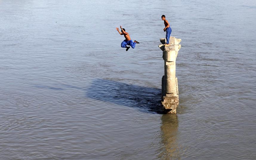 شابان يقفزان في نهر ساردارياب للتغلب على حرارة الشمس الحارقة في بيشاور.
