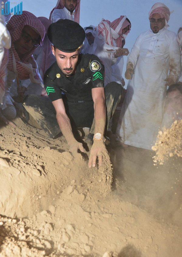 صورة مؤثرة لرجل أمن يُشارك في دفن زميله الشهيد عوض المالكي