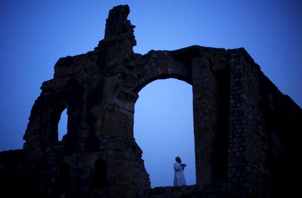 صورة لرجل يدعو الله سبحانه وتعالى قرب أنقاض مسجد فيروز شاه كوتلا في نيودلهي