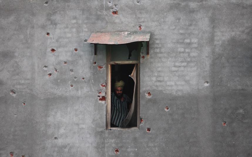 رجل يطل من نافذة منزله التي تضررت من الرصاص بعد هجوم في ولاية شمال البنجاب