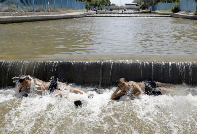 مجموعة من الأطفال يلهون في قناة مياه في أورومتشي