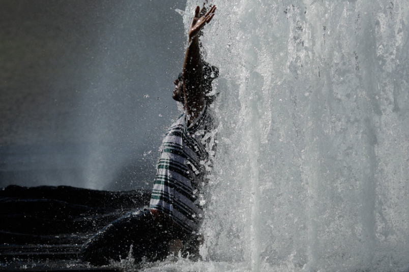 رجل يجلس أسفل نافورة مياه في يوم صيفي حار في برلين.