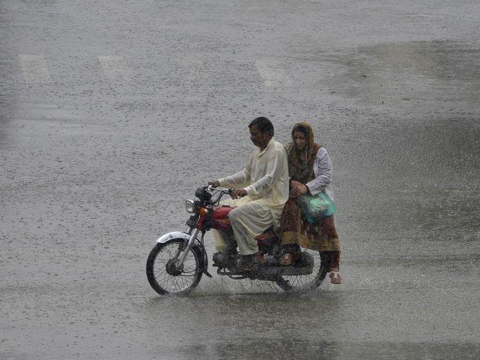 رجل باكستاني يركب على درجاته النارية مع سيدة خلال يوم ماطر