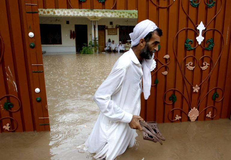 رجل يسير في مياه الفيضانات في باكستان