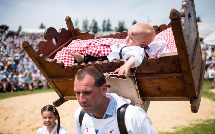 رجل يحمل طفلا صغيرا في المهد خلال مهرجان المصارعة في جبال الألب