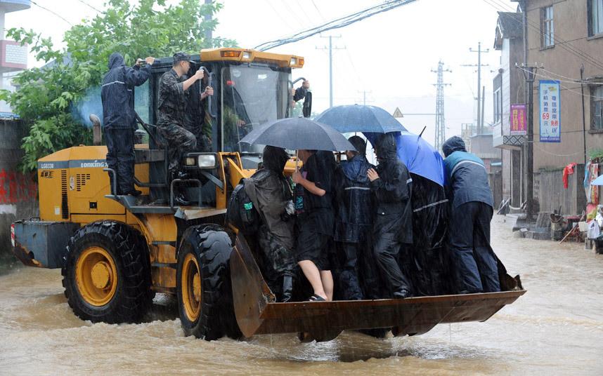 جرافة تقوم بنقل السكان من منطقة غمرتها المياه بفعل الأمطار الغزيرة في الصين
