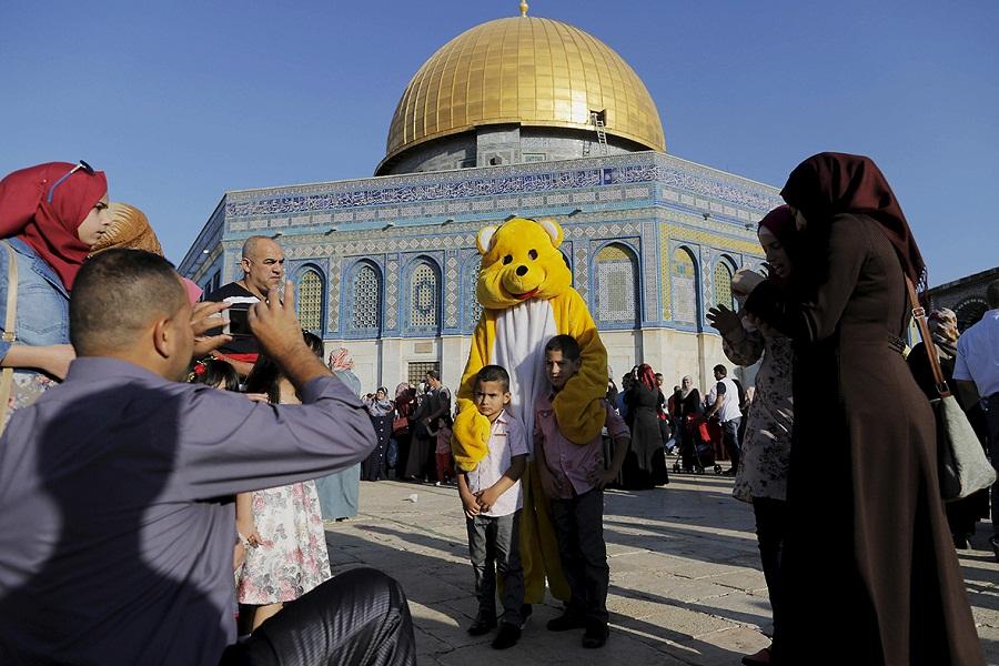 أطفال فلسطينيين يلتقطون صورة بأول أيام عيد الفطر السعيد في باحات مسجد قبة الصخرة