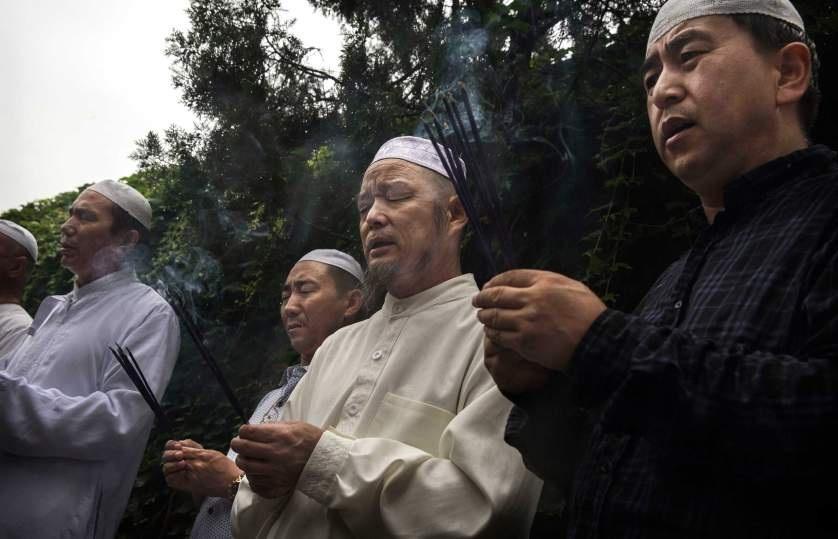 """المسلمون من أقلية """"هوي"""" يشعلون البخور قرب قبر الإمام بأول أيام عيد الفطر السعيد في مسجد نيوجيه التاريخي في بكين"""