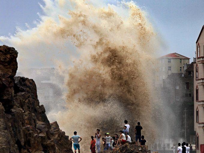 سكان يتجمعون لمراقبة موجات ضخمة وصلت إلى مقاطعة تشجيانغ