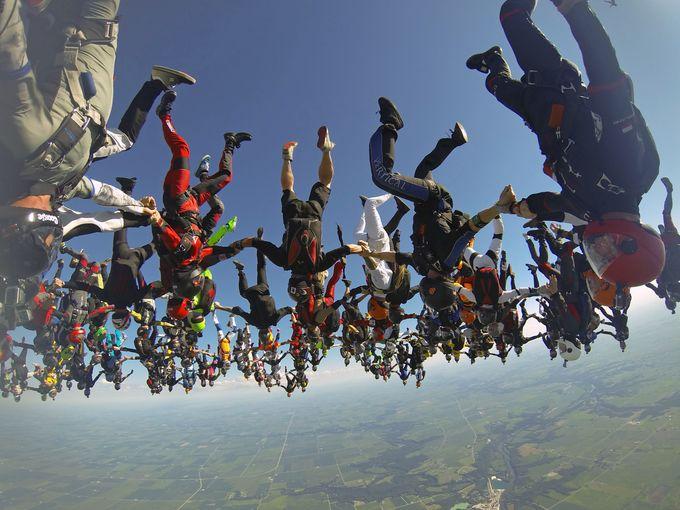 أعضاء فريق دولي من هواة القفز بالكظلات يتشابكون في الهواء لتحطيم رقم قياسي عالم جديد بالقفز بالمظلات.