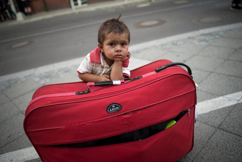 طفل يرتكز على حقيبة في انتظار والديه للخروج من مكتب ولاية برلين للشؤون الصحية