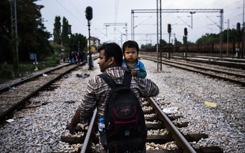 رجل يحمل طفله ويمشي على سكة قطار بانتظار الرحلة إلى بلدة غيفيغليا