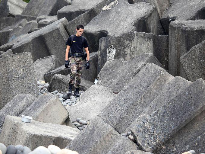 ضابط شرطة من قوات درك سانت بنوا يتفقد الشاطئ للبحث عن حطام الرحلة MH370