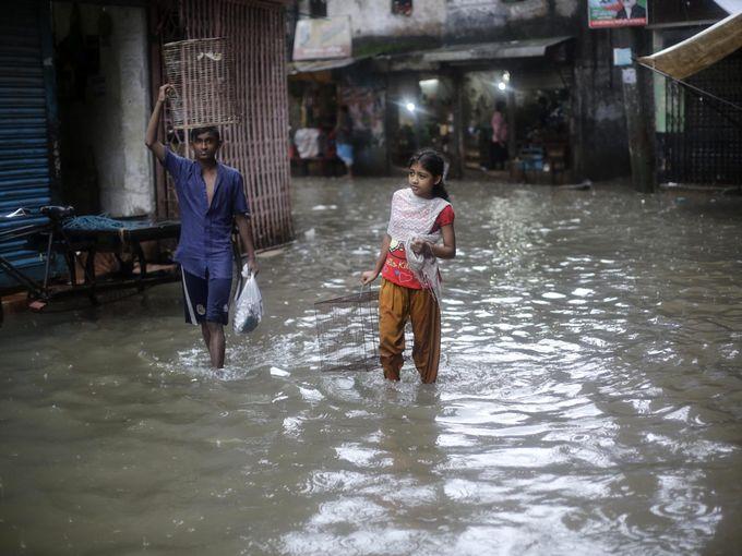 صبي وفتاة يعبران شارع غمرته مياه الفيضانات بعد الأمطار الموسمية الغزيرة في دكا.