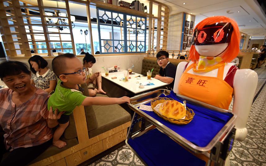 نادلة روبوت تقدم الوجبات للزبائن في مطعم في هايكو